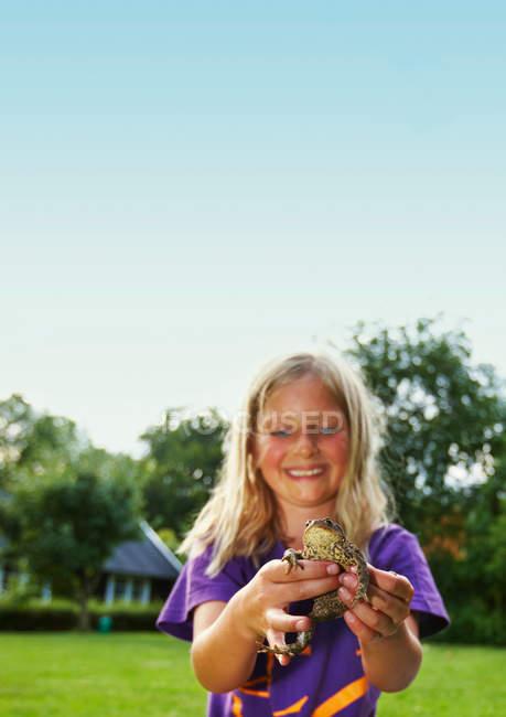 Девушка держит лягушку на заднем дворе, сосредоточиться на переднем плане — стоковое фото