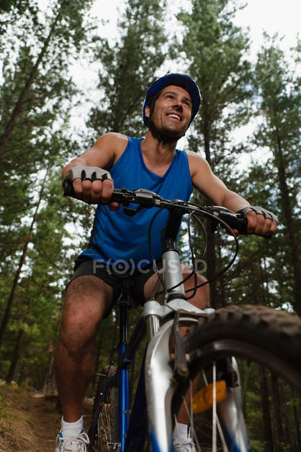 Low angle view of Man mountain biking in forest — Stock Photo