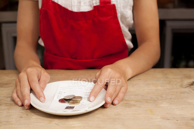 Close up of waitress with bill and gratuity at kitchen counter — Stock Photo