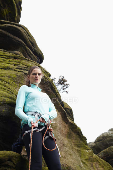Rock climber tying ropes by boulder — Stock Photo
