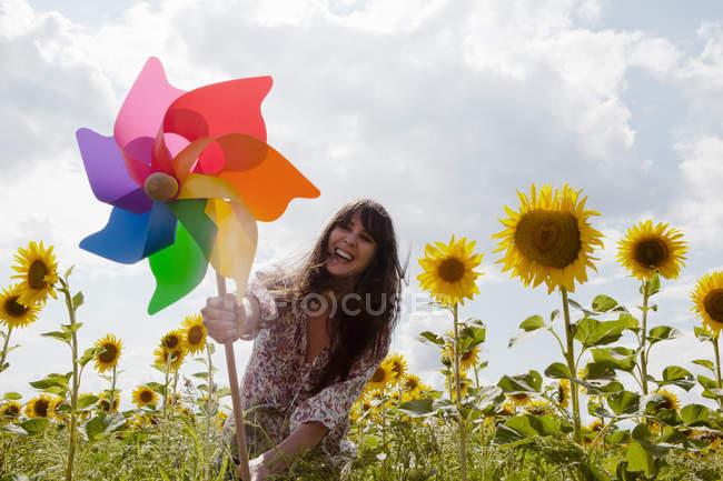 Женщина держит мельницу в поле подсолнухов — стоковое фото