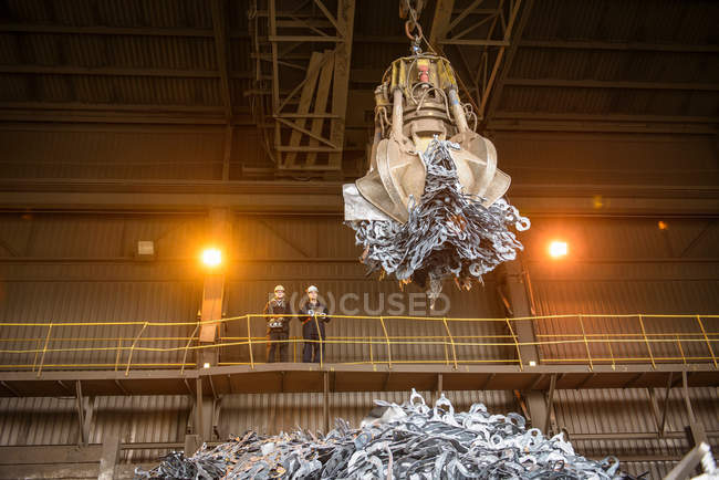 Low angle view of workers watching scrap metal grab in steel foundry — Stock Photo