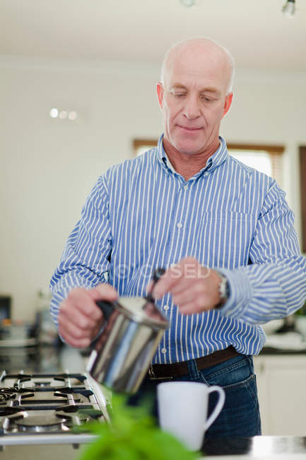 Older man pouring cup of coffee — Stock Photo