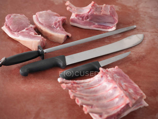 Cuchillos con los cortes de carne de cerdo - foto de stock