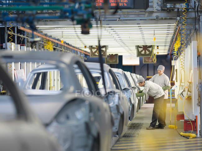 Рабочие автозавода на производственной линии — стоковое фото