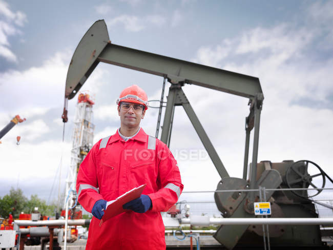 Worker looking to camera, standing in front of an oil pump above an onshore oil well (nodding donkey/pumpjack) - foto de stock