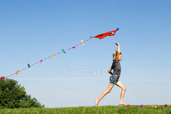Girl playing with kite outdoors — Stock Photo
