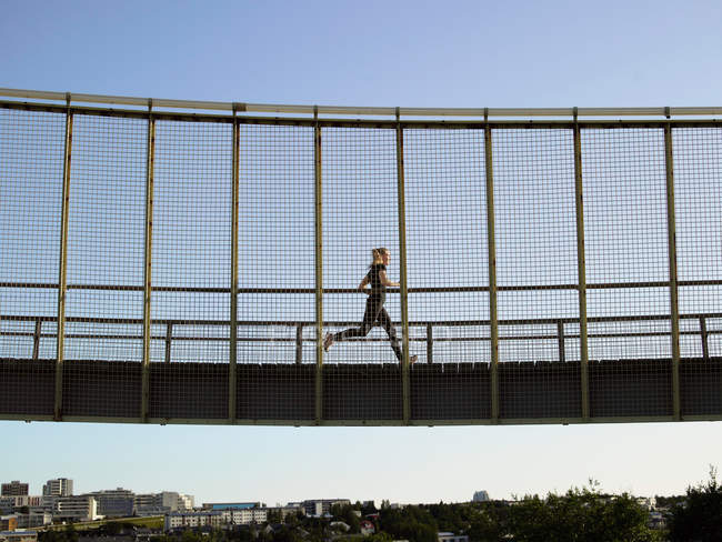 Runner crossing skybridge at daytime — Stock Photo