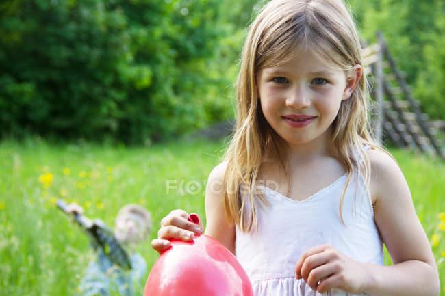 Chiudi ritratto di giovane ragazza con palloncino rosso in mano — Foto stock