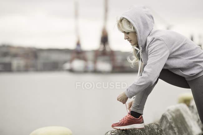 Femelle coureur attachant lacets formateur sur quai — Photo de stock
