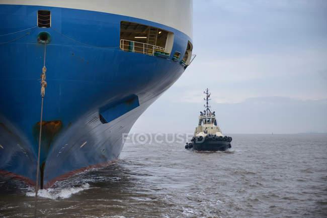 Cropped image of Tug alongside large ship out to sea — Stock Photo