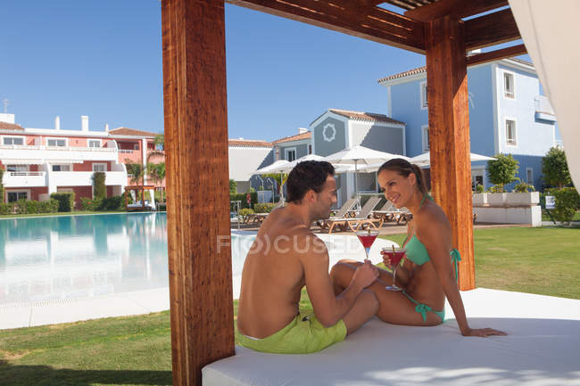 Young couple sitting on sunlounger at holiday resort with cocktails — Foto stock
