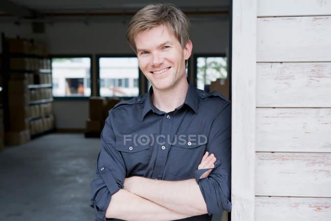 Uomo sorridente in piedi in garage — Foto stock