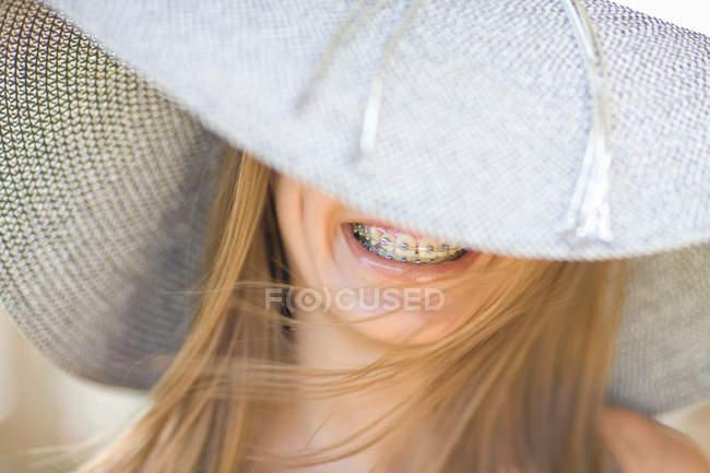 Smiling girl in braces wearing sunhat — Stock Photo