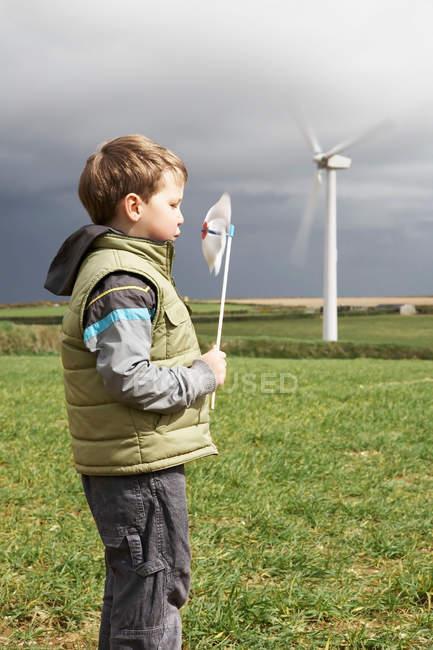 Мальчик дует мельница на ферме ветра — стоковое фото