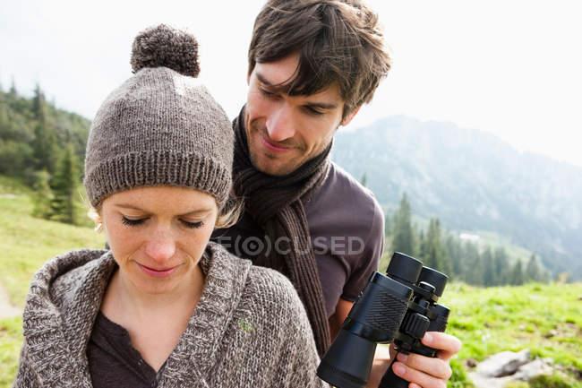 Mann bietet Frau Fernglas an — Stockfoto