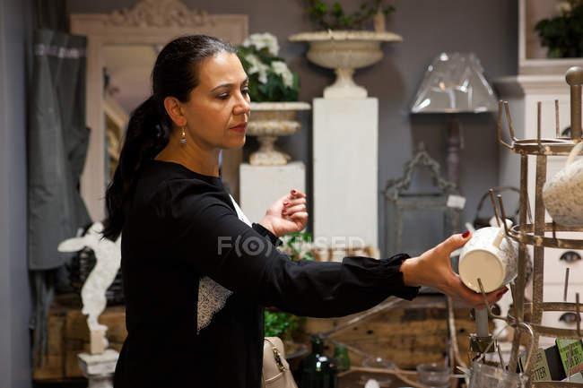 Mature female shopper browsing mugs in gift shop — Stock Photo
