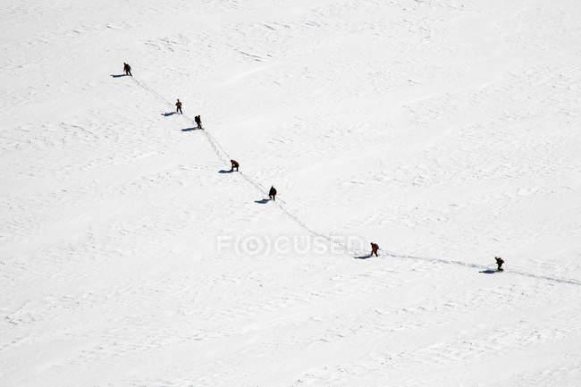 Vista aerea di montagna innevata con distante gruppo di escursionisti — Foto stock