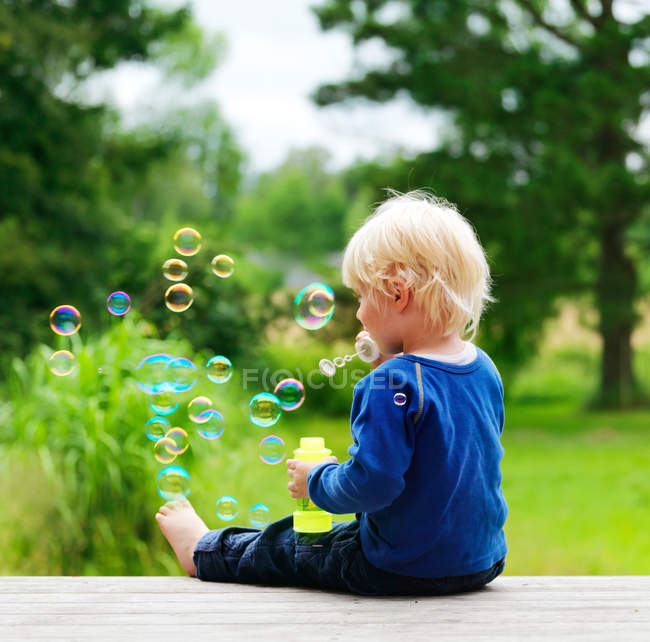 Boy blowing bubbles on porch — Stock Photo