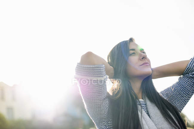 Young woman with hands behind head in sunlight — Stock Photo