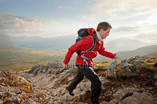 Randonneur marchant sur le sommet d'une montagne rocheuse — Photo de stock