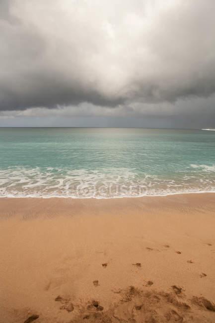Storm cloud over sandy beach — Stock Photo