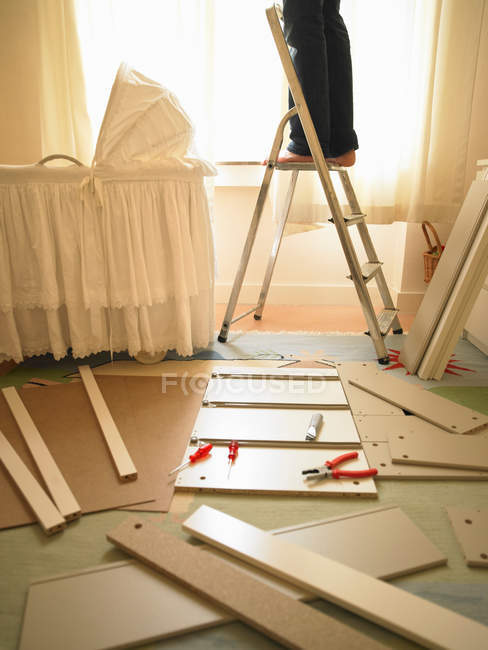 Man standing on ladder in baby room — Stock Photo
