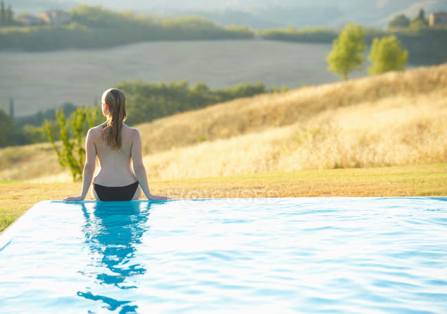 Woman sitting at edge of pool — стоковое фото