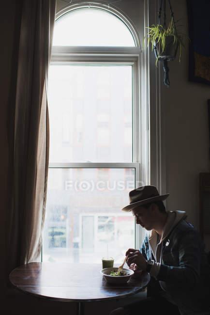 Молодой человек, сидя за столом, окно, здоровой пищи — стоковое фото