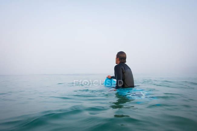 Mann sitzt auf Surfbrett im Ozeanwasser — Stockfoto