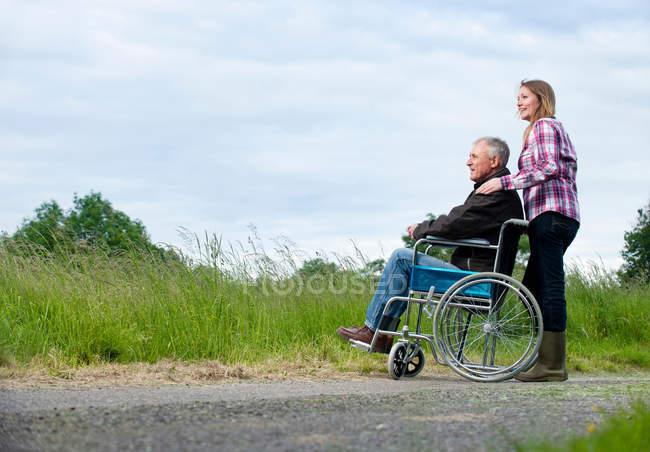 Frau schiebt Vater im Rollstuhl — Stockfoto