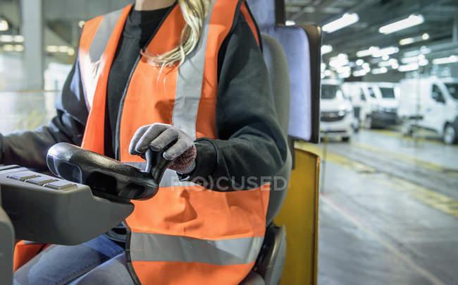 Женщина-водитель погрузчика на автомобильном заводе, крупным планом — стоковое фото