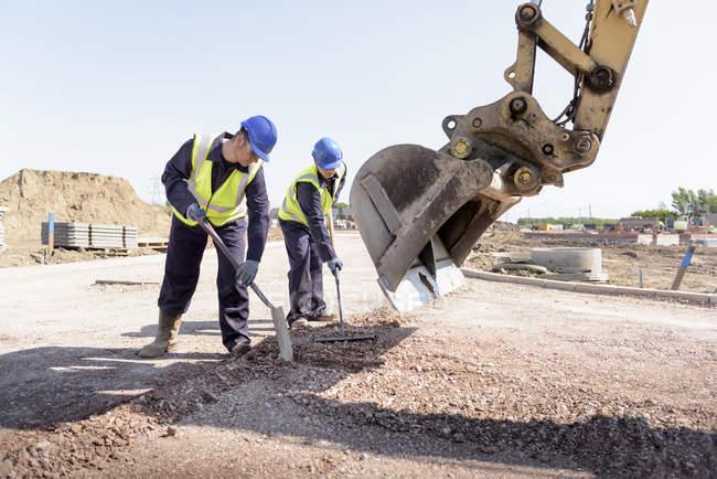 Учень будівельників вирівнювання доріг з екскаватор на місці будівництва — стокове фото