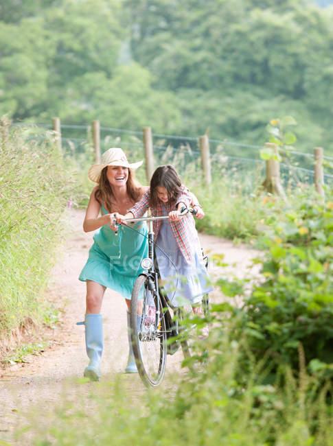 Madre con hija en bicicleta - foto de stock