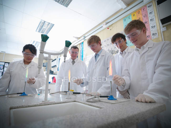 Science teacher and students conducting experiment in school laboratory — Stock Photo