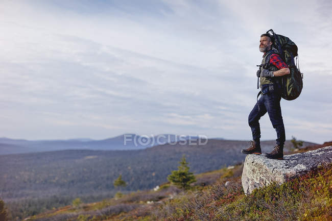 Hiker with backpack overlooking mountains, Lapland, Finland — Stock Photo