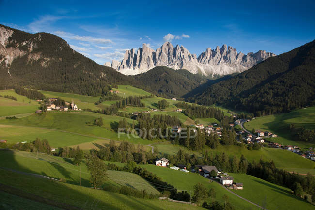 Rocky mountains above green rural valley — Stock Photo