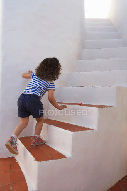 Rear view of girl carefully climbing steps — Stock Photo