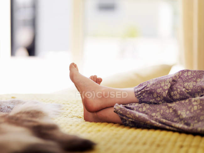 Cropped shot of girl feet on bed — Stock Photo