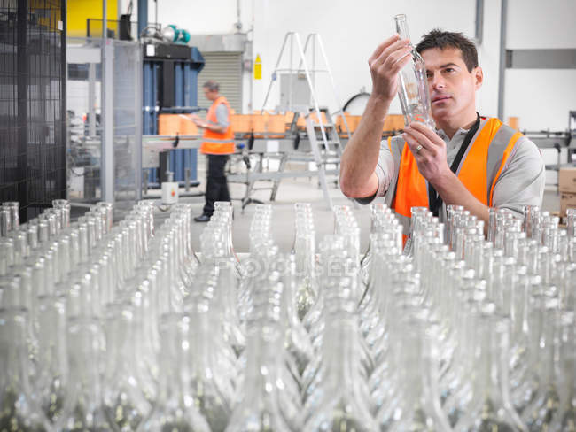Работник завода осматривает бутылки — стоковое фото