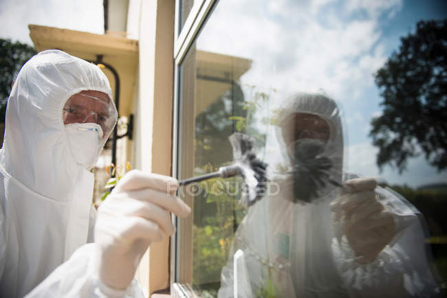 Forensic scientists dusting window for finger prints at crime scene — Stock Photo