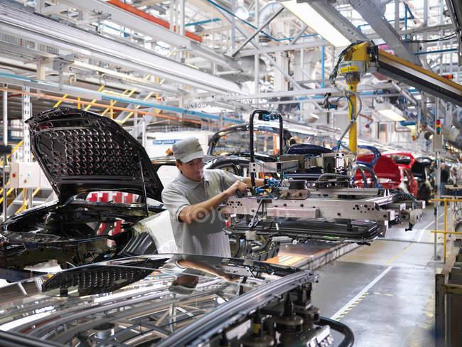 Рабочий автозавода на производственной линии — стоковое фото