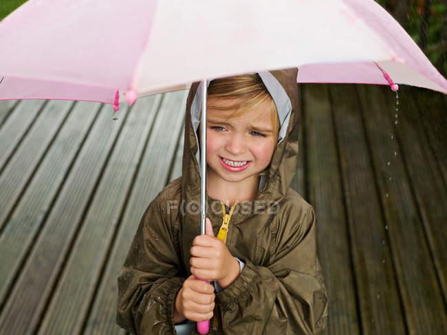 Une jeune fille sous un parapluie — Photo de stock