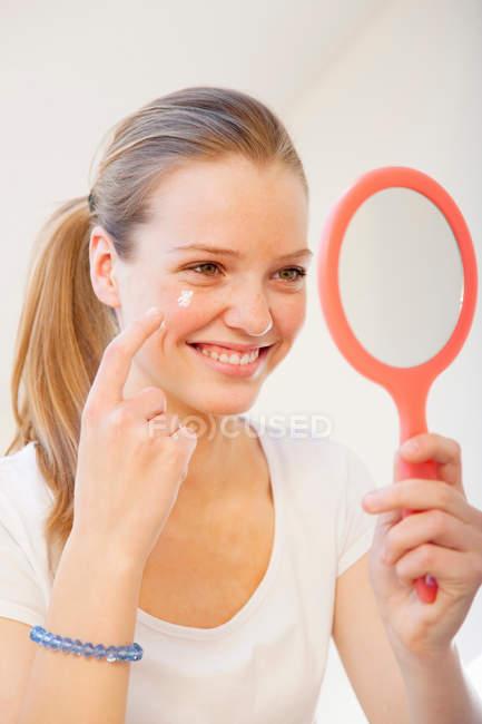 Adolescente aplicación de maquillaje en el espejo - foto de stock