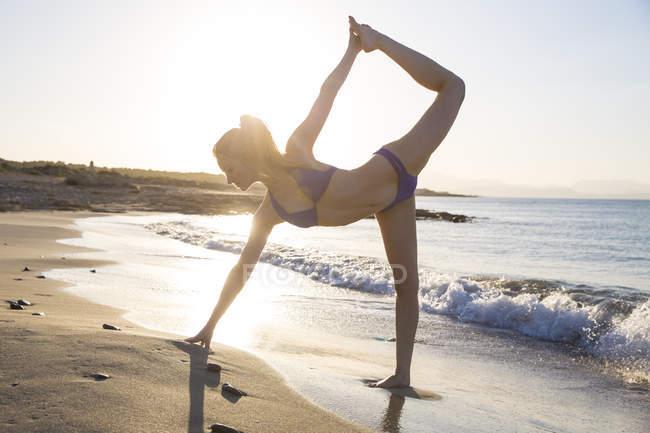 Junge Frau steht am Strand in Yogaposition — Stockfoto