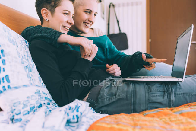 Young lesbian couple reclining on bed pointing at laptop — Stock Photo