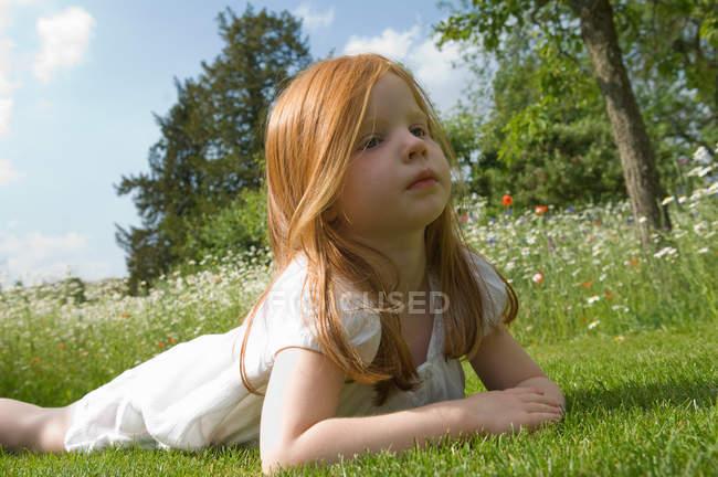 Девушка, лежащая на траве в поле цветов — стоковое фото