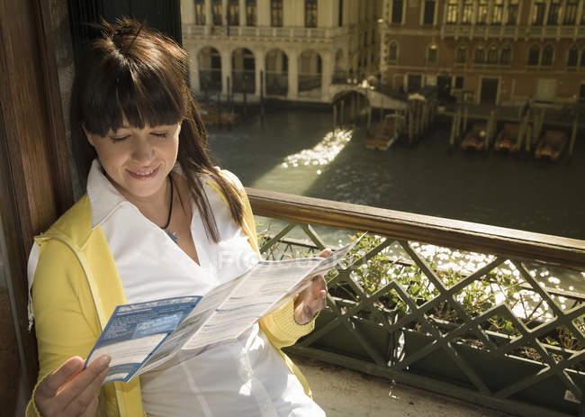 Giovane donna che guarda la mappa sul finestrino dell'hotel sopra Canal Grande, Venezia, Italia — Foto stock