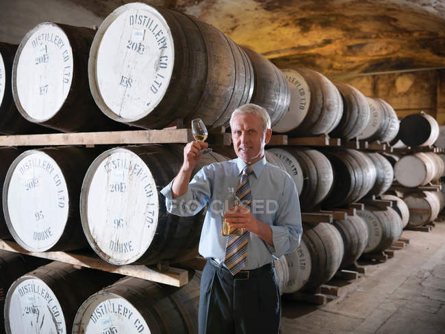 Gerente com amostra de uísque ao lado de barricas de uísque envelhecidas em destilaria — Fotografia de Stock