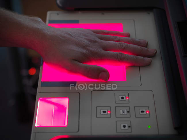 Людина сканування руку для відбитки пальців на машині в лабораторії — стокове фото